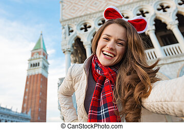 Smiling woman tourist taking Christmas selfie in Venice,...