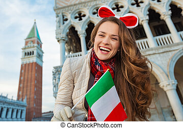 Woman tourist showing Italian flag on Piazza San Marco in...