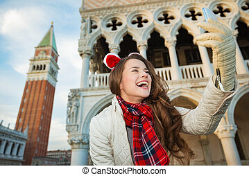 Happy woman tourist taking Christmas selfie in Venice, Italy...