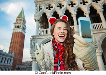 Woman taking Christmas selfie and showing victory in Venice...