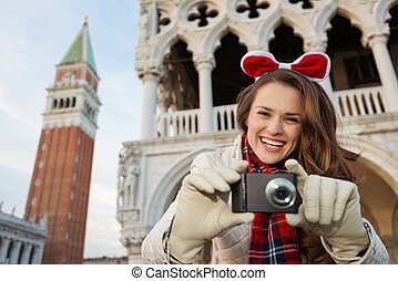 Happy woman tourist with camera on Christmas in Venice,...