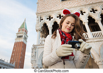 Woman tourist checking photos while on Christmas Venice -...