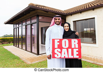 muslim couple holding for sale sign in front of their house