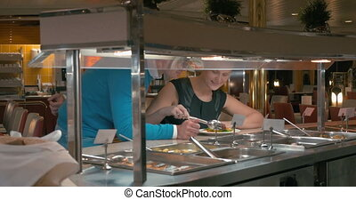 Young couple taking food in self-service cafe - Young man...