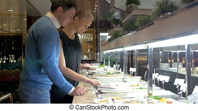 Couple by Self-Service Buffet - Young couple is choosing...