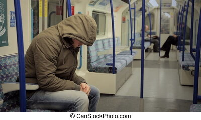 Man with hoodie on a tube train - LONDON - Man with a hoodie...