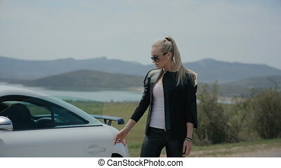 Self-confident woman on the road beside her expensive car -...