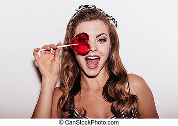 Sweet look. Cheerful young woman looking threw a lollipop...