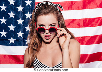 I am watching you. Beautiful young woman looking over sunglasses while standing against American flag