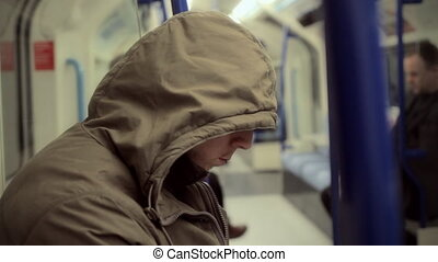 Man with hoodie in a tube coach - LONDON - Man with hoodie...