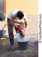 man pours a bag of cement in bucket