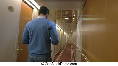 Adult Man Walking Along A Corridor Of Ocean Cruise Ship -...