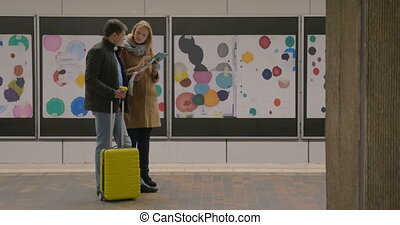 Young travelers with coffee and pad in subway - Young couple...