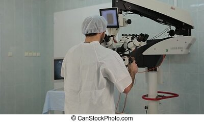 Man using a big microscope system in a medical laboratory -...