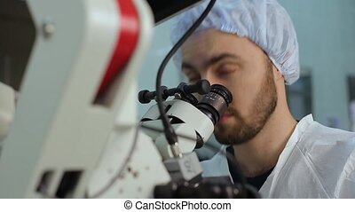 Young doctor using loking at eyepieces of microscope complex system in a hospital laboratory