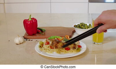 Man is Putting Hot chicken leg on Plate With pasta - Man is...