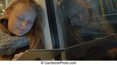 Woman Using Tablet In Subway Train - Smiling caucasian woman...