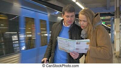 Couple of travelers with map in subway