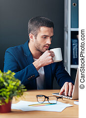 No time for break. Handsome young man in smart casual wear working on laptop and holding coffee cup while sitting at his working place in office