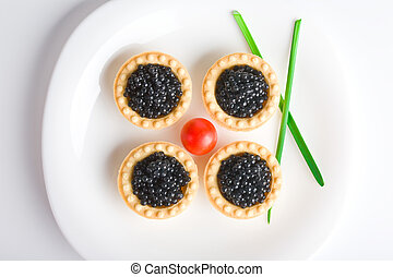 Tartlet with black caviar on a white platter