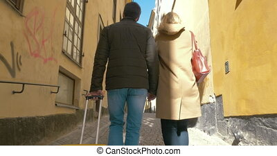Couple of tourists with roll-on bag walking in old street -...