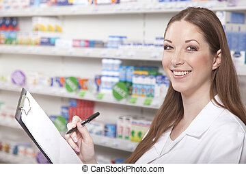 Pharmacist with clipboard while stocktaking in pharmacy