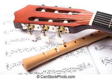 Guitar and wooden flute on sheet music Close up