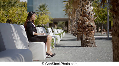 Businesswoman sitting working in an urban park