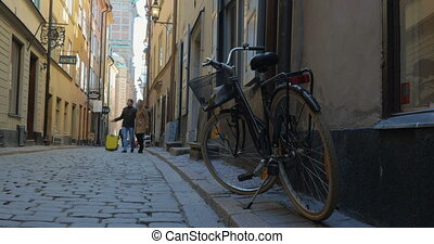 Man and woman with travel bag wandering in old city street -...