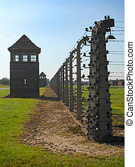 Auschwitz Birkenau - Fence, wire and a watchtower in...