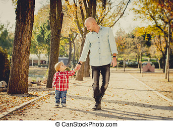 young father and his beautiful little 2 years old son walking together