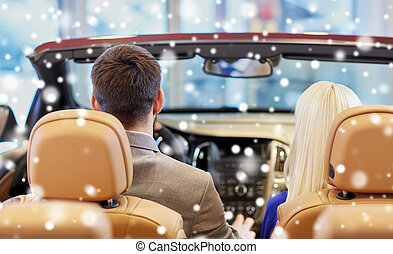 couple sitting in cabrio car at auto show - auto business,...