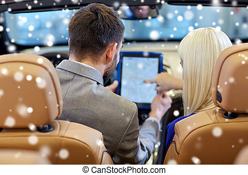 couple sitting in cabrio car with tablet pc - auto business,...