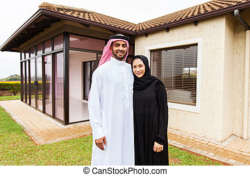 young muslim couple standing in front of their house -...
