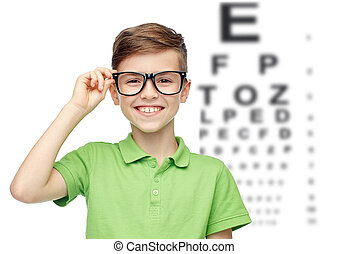 happy boy in eyeglasses over eye chart - childhood, vision,...