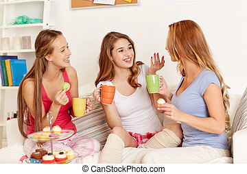 happy young women drinking tea with sweets at home -...