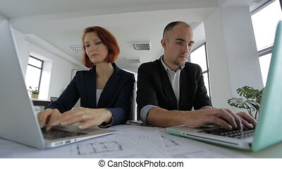 Businesswoman and Businessman in suits sitting in a large bright spacious office, each busy with his part of the work.