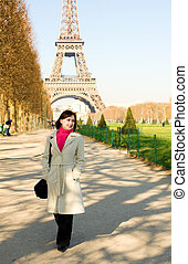 Happy beautiful woman in Paris walking near the Eiffel Tower