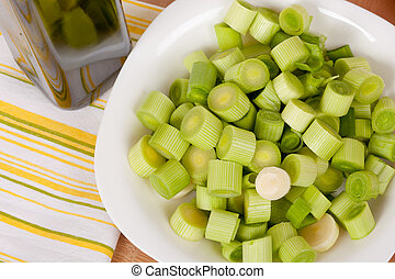 Fresh chopped leeks on a wooden board with red tomatoes