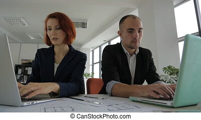 man and woman in suits sitting in a large bright spacious office and working together on one project.