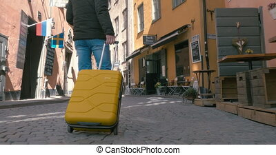 Back View Of A Traveling Man Walking With Suitcase -...
