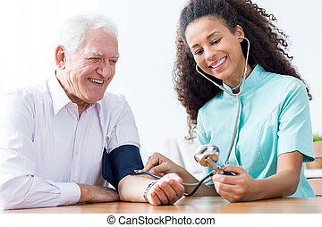 Man having measured blood pressure - Smiling senior man...