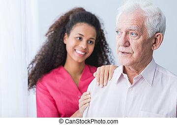 Female carer assisting senior man