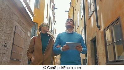 Young couple with pad walking in old narrow street -...