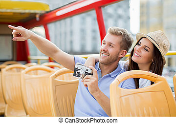 Happy couple - Smiling tourists with camera in a tour bus