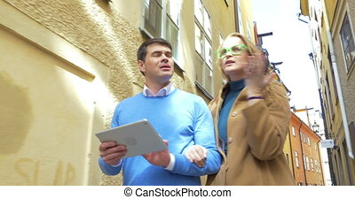 Couple of tourists with tablet PC wandering in old city -...