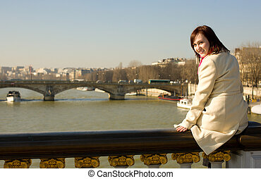 Happy beautiful girl in Paris sitting on the balustrade of Pont Alexandre III