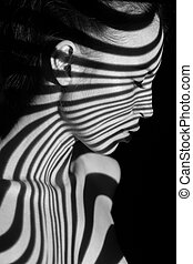 The face of woman with black and white zebra stripes - The...