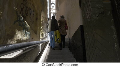 Two tourists walking in old narrow street, Stockholm -...