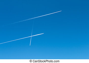 Jet Trails Pattern On Blue Sky - Three jet trails with two...